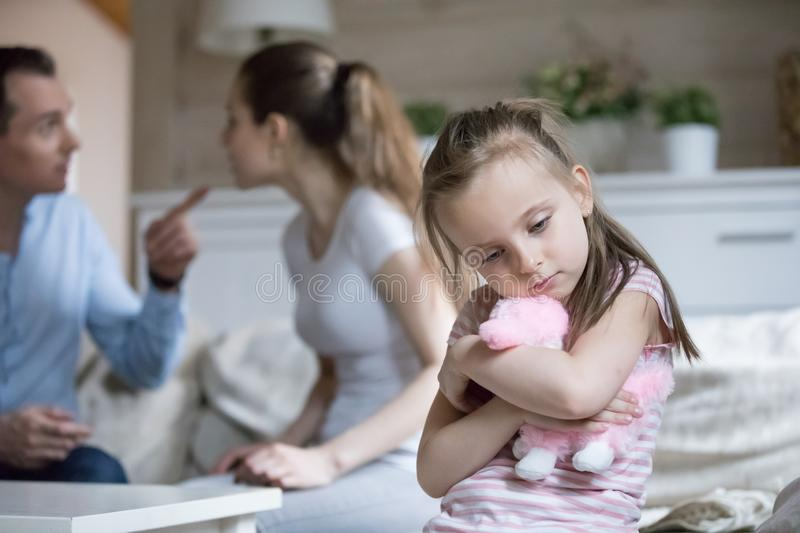 Lonely little girl feel sad because of parents fighting. Sad little girl hug toy upset with parents fighting, frustrated small girl feel alone and depressed, mom royalty free stock image