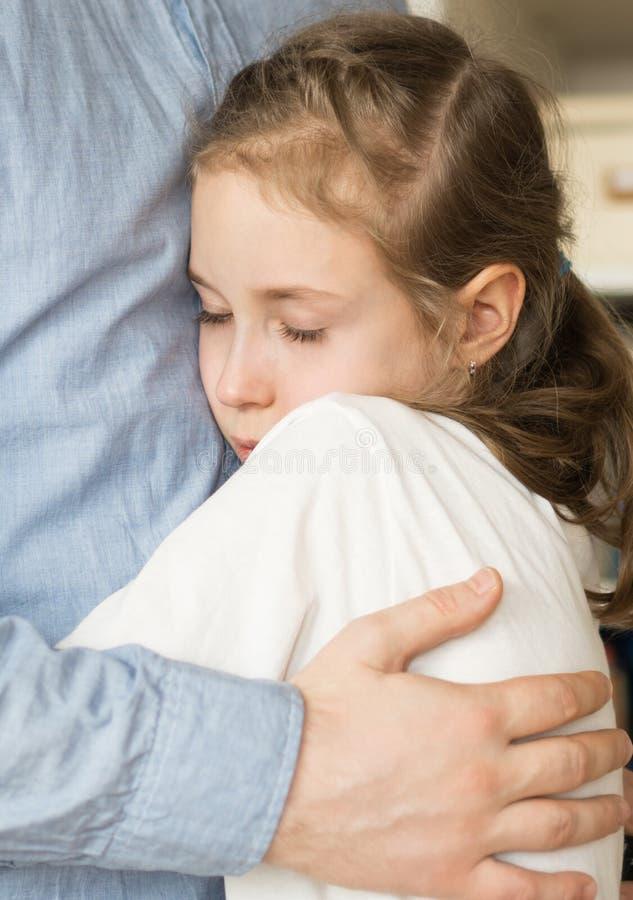 Girl hugging her dad. Sad little girl hugging her dad royalty free stock image