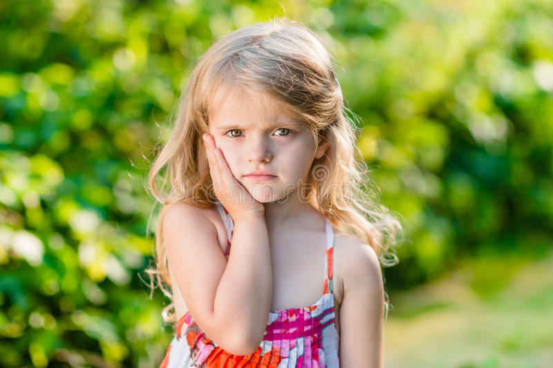 Sad little girl with long blond hair suffering from toothache. Sunny summer day in beautiful green park stock photography