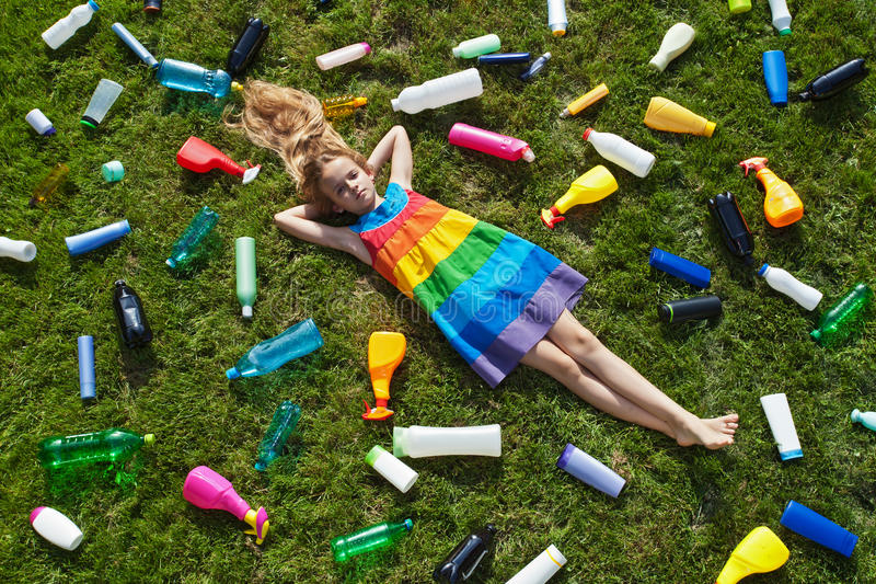 Sad little girl lying on the garbage filled grass royalty free stock image