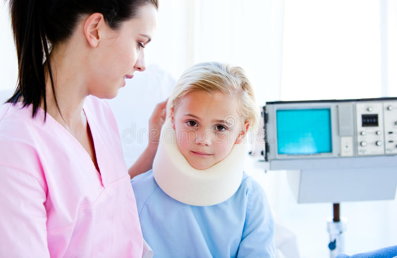 Sad little girl with a neck brace with her nurse. Sad little girl with a neck brace sitting with her nurse on a hospital bed royalty free stock photos