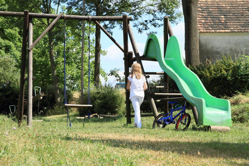 Sad little girl on playground. Sad kid - lonely blond girl in white clothes on kids playground with green slide, swing and blue bicycle stock photo