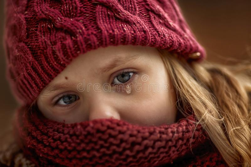 Sad little girl portrait with accent on eyes with tear. Close up Sad little girl portrait with accent on eyes with tear royalty free stock image