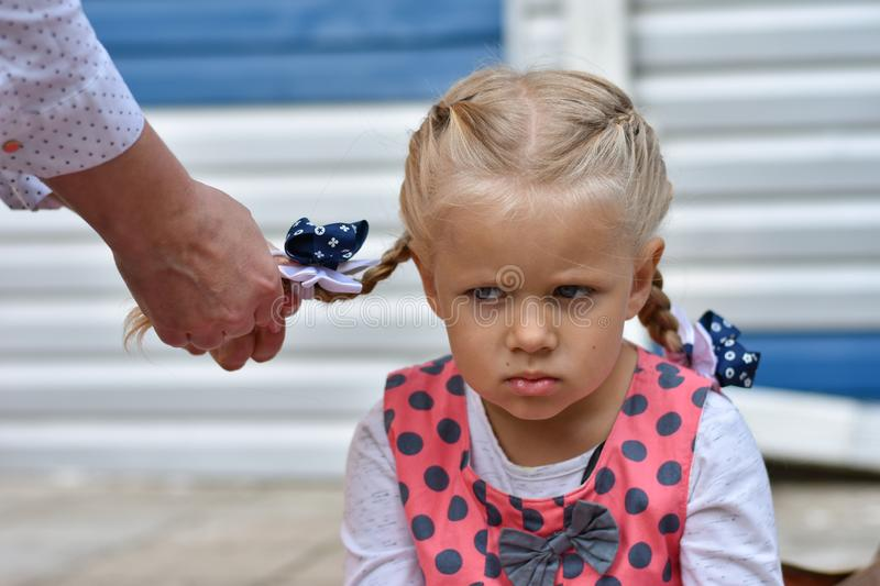 Sad little girl sits and waits while mom braids her hair from her hair. Sad little girl sits and waits while mom braids her hair from hair stock images