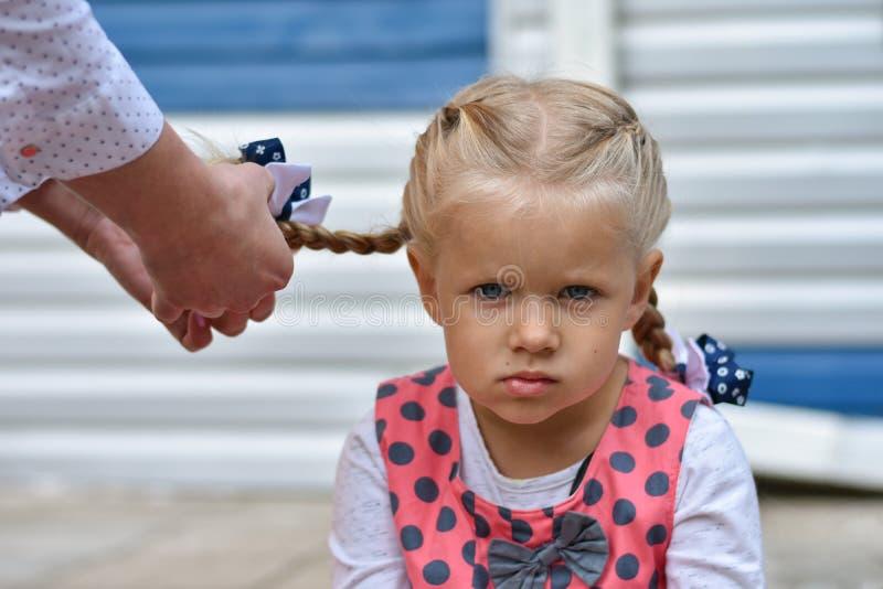 Sad little girl sits and waits while mom braids her hair from her hair. Sad little girl sits and waits while mom braids her hair from hair stock photos