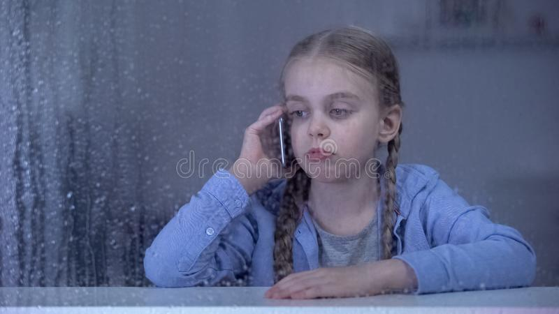 Sad little girl talking phone on rainy day, staying home alone, missing mother royalty free stock image