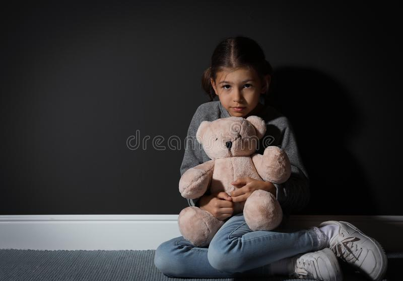 Sad little girl with teddy bear near black wall. Domestic violence concept. Sad little girl with teddy bear near black wall, space for text. Domestic violence royalty free stock images