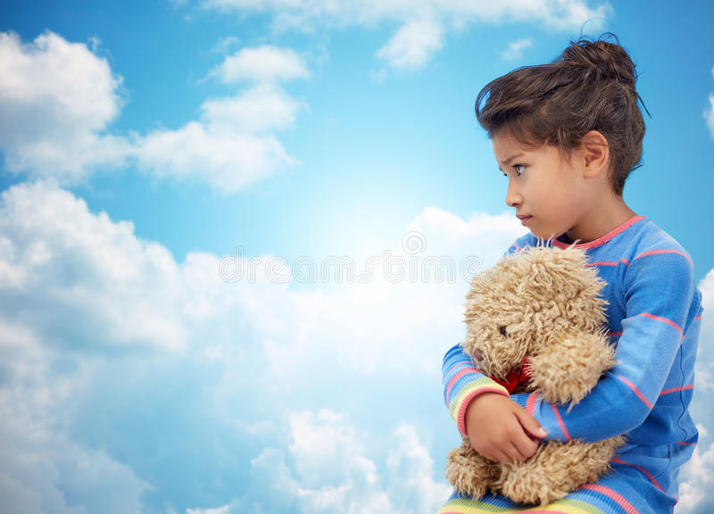 Sad little girl with teddy bear toy over blue sky. Childhood, sadness, loneliness and people concept - sad little girl with teddy bear toy over blue sky and royalty free stock images