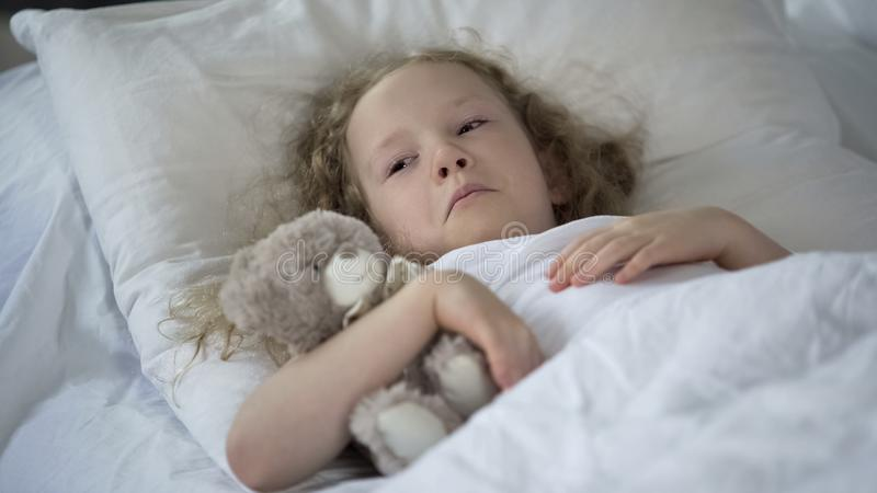 Sad little girl with toy crying in bed, unhappy sick child feeling lonely stock photography