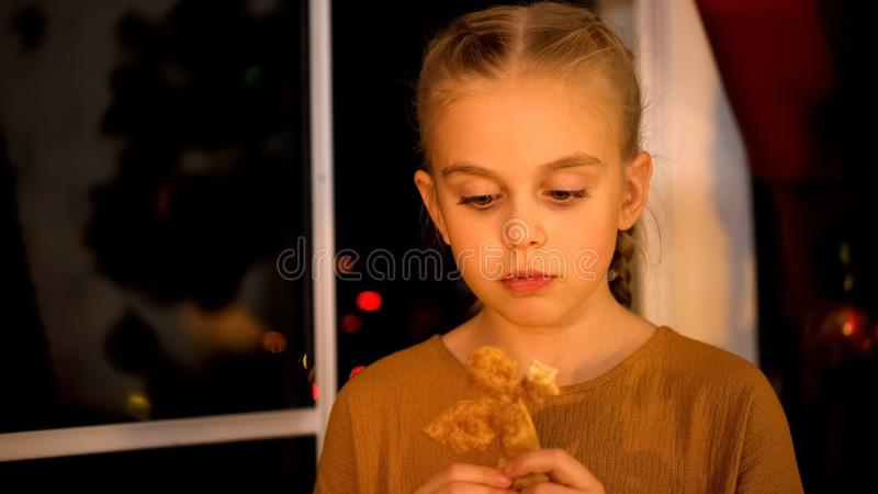 Sad little girl waiting for parents near orphan home window, eating Xmas cookie royalty free stock photos