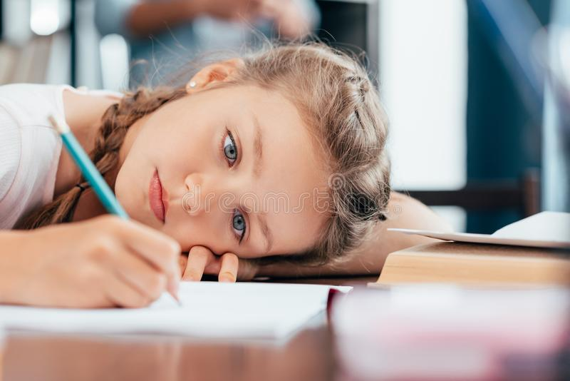 sad little girl writing stock photos