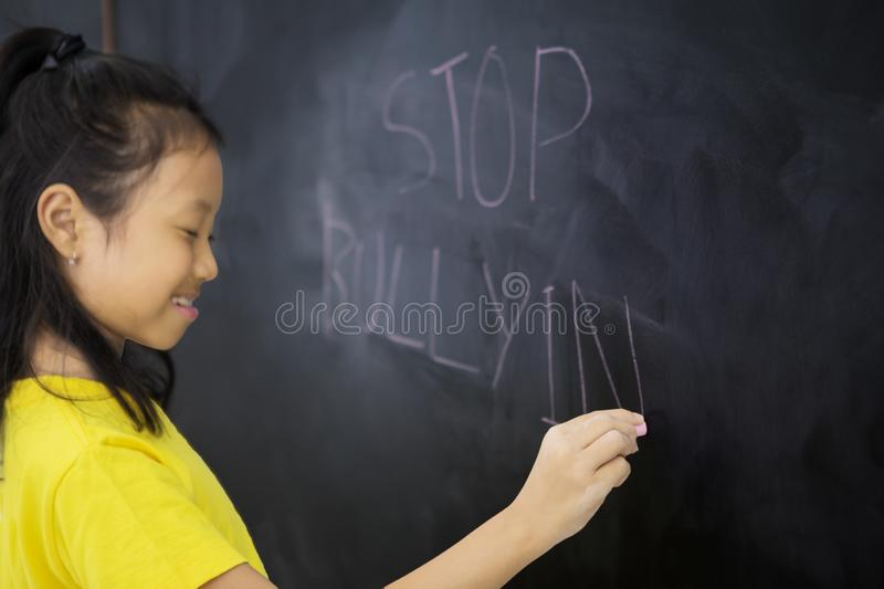 Sad little girl writing a text of stop bullying royalty free stock photography
