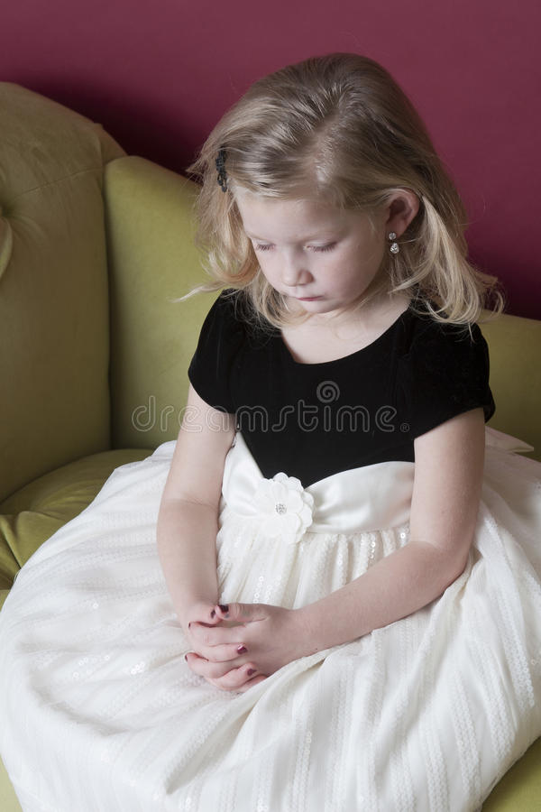 Sad little model. Very sad little girl sitting on couch stock image