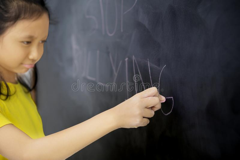 Sad little schoolgirl writing a text of stop bullying stock photo