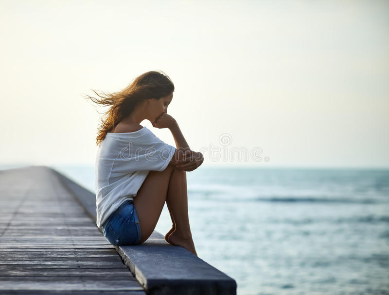 Sad lonely beautiful woman sitting on the pier royalty free stock photos