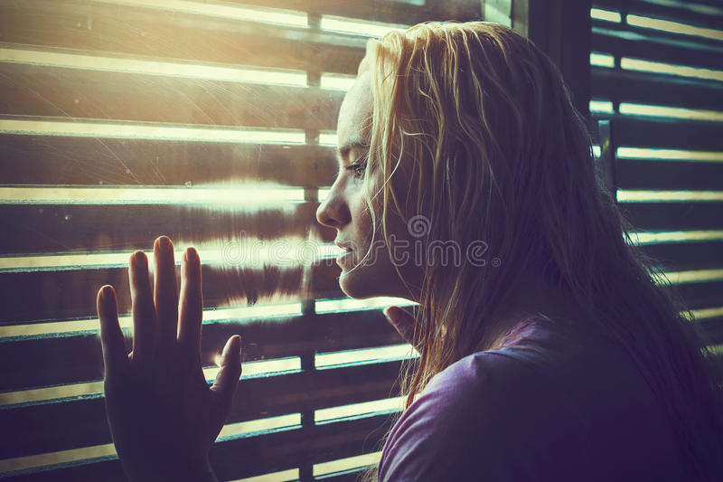 Sad and lonely blonde woman with wet hair royalty free stock image