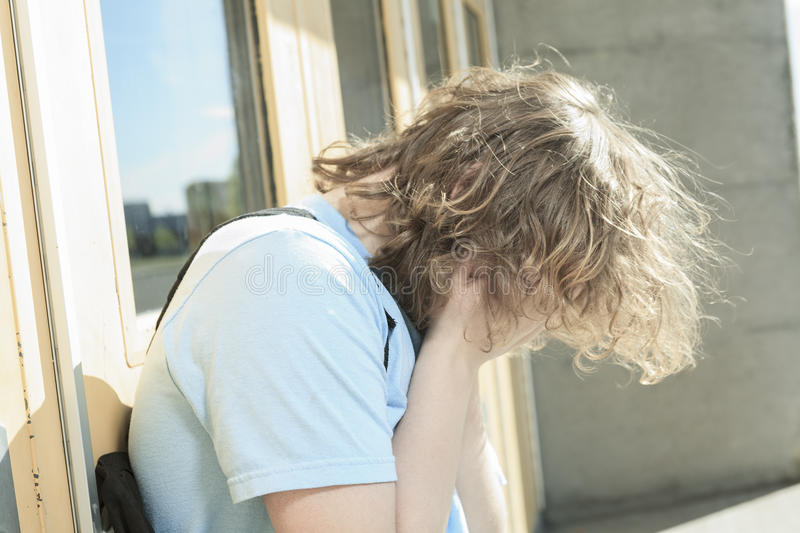 Sad lonely boy in the school playground royalty free stock photos