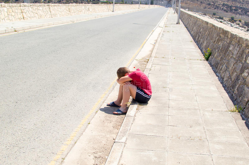 Sad and lonely boy. Sitting alone on an empty road in the middle of nowhere royalty free stock photo