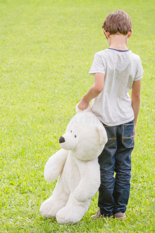 sad lonely boy with teddy bear standing in the meadow