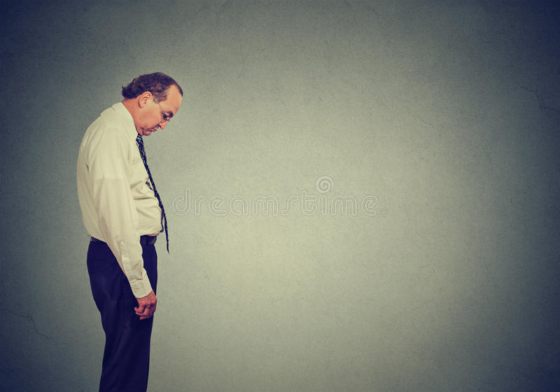 Sad lonely business man looking down has no energy motivation in life depressed stock photography