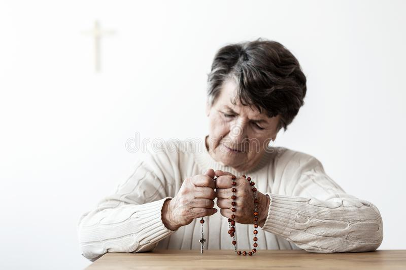 Sad and lonely grandmother with rosary praying to god in the church royalty free stock photo
