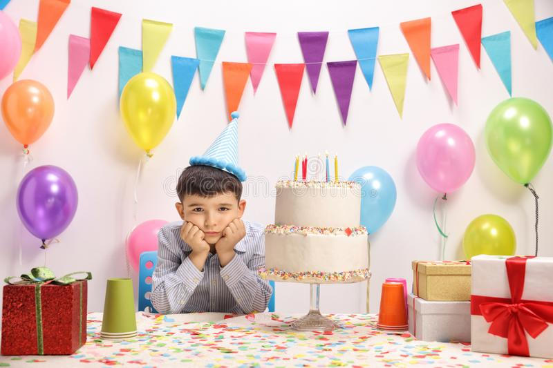Sad and lonely little boy with a party hat stock photography