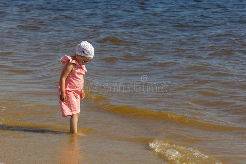 Sad lonely little girl looking away and waiting for somebody hopefully on the summer beach washed by waves royalty free stock photography