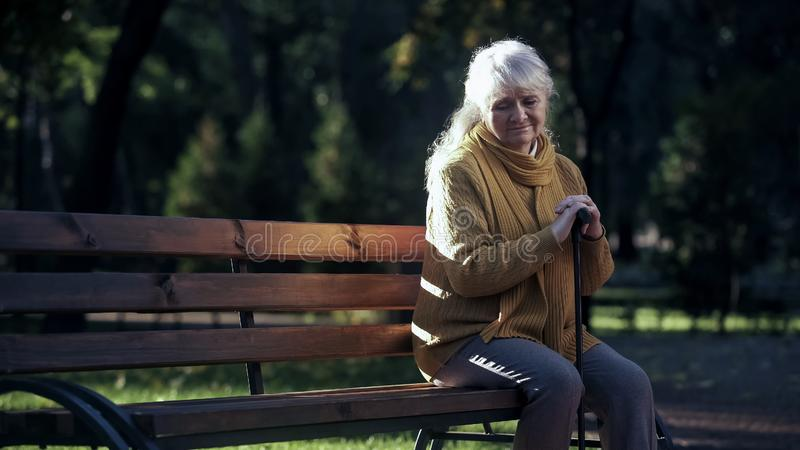 Sad lonely old woman sitting on bench in park, abandoned elderly people alone royalty free stock photos