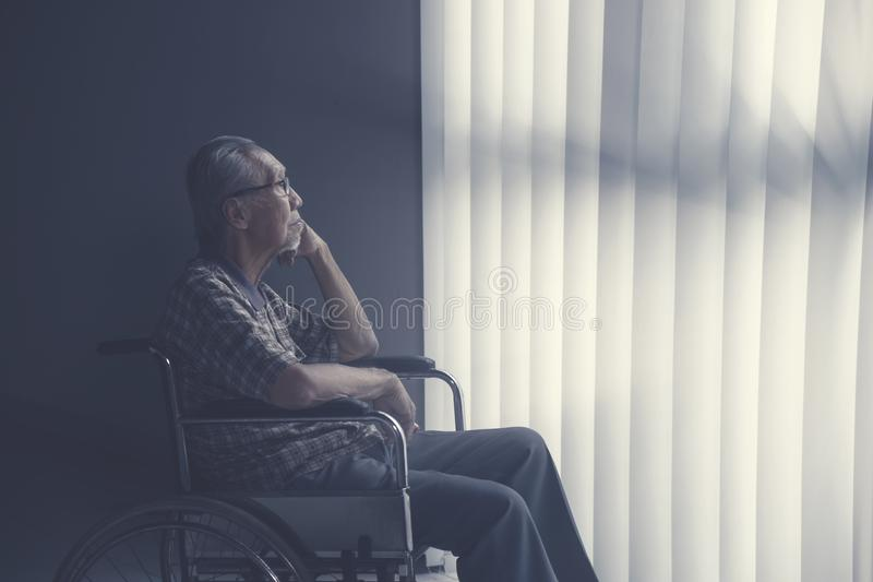Sad lonely senior man sitting on wheelchair royalty free stock image