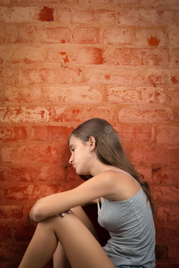 Sad and lonely teenage girl sitting on the floor royalty free stock photos