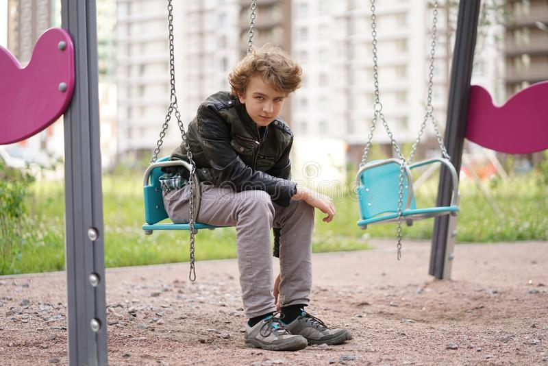 Sad lonely teenager outdoor on the Playground. the difficulties of adolescence in communication concept. stock image