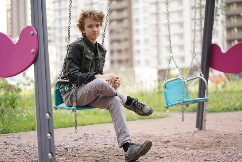 Sad lonely teenager outdoor on the Playground. the difficulties of adolescence in communication concept. stock photography