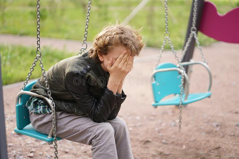 Sad lonely teenager outdoor on the Playground. the difficulties of adolescence in communication concept. Alone royalty free stock photography