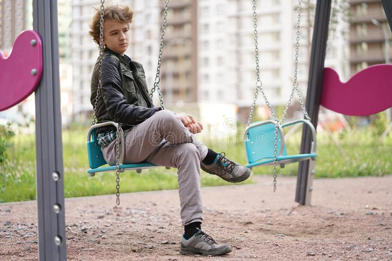 Sad lonely teenager outdoor on the Playground. the difficulties of adolescence in communication concept. Alone royalty free stock photo