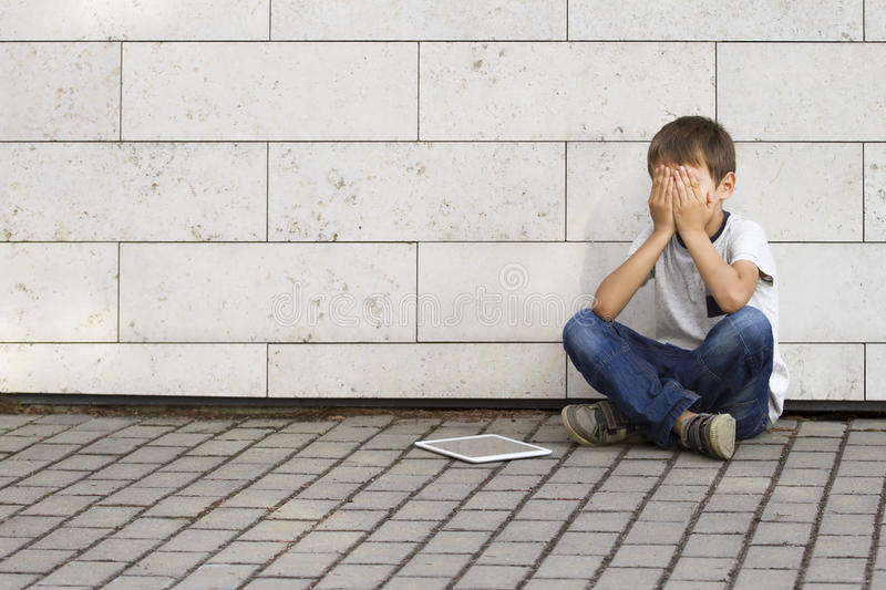 Sad, lonely, unhappy, disappointed child sitting alone on the ground. Boy holding his head, look down. The tablet pc royalty free stock photography