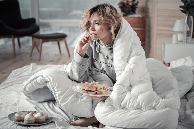 Sad and lonely woman eating burger and French fries in the bed royalty free stock photography