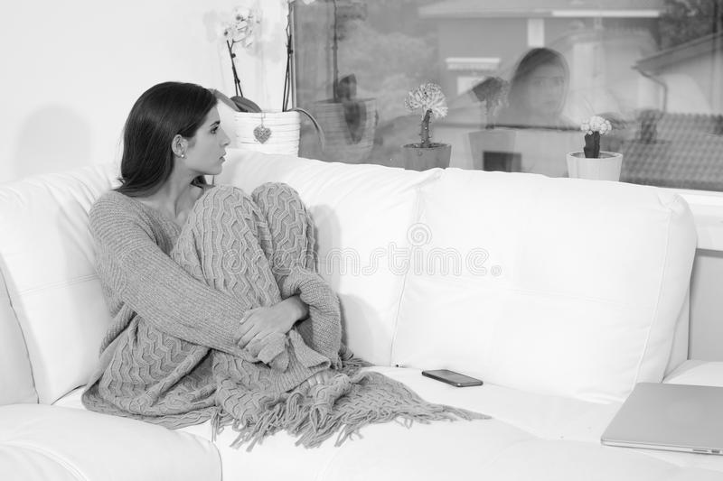 Sad lonely woman at home in winter pensive heart broken black and white looking out of window royalty free stock photos
