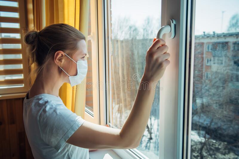 Sad lonely woman in protective medical mask on her face looking at window. Chinese pandemic coronavirus, virus Covid-19. Quarantine, prevent infection, home royalty free stock photos