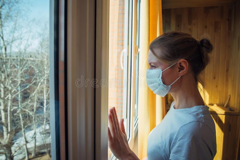 Sad lonely woman in protective medical mask on her face looking at window. Chinese pandemic coronavirus, virus Covid-19. Quarantine, prevent infection, home stock photos