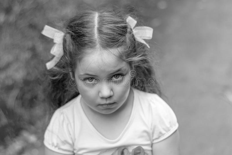 Sad look of little girl outdoor. Close up portrait royalty free stock images