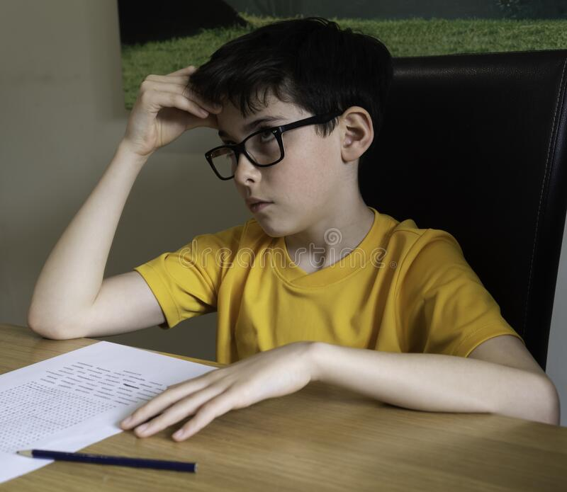 Sad looking boy doing homework during quarantine time royalty free stock image