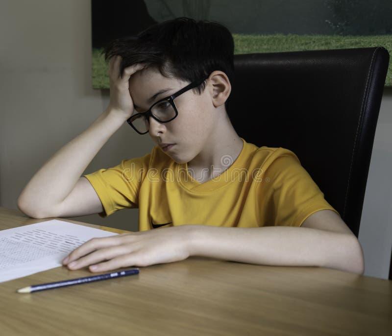Sad looking boy doing homework during quarantine time stock photography