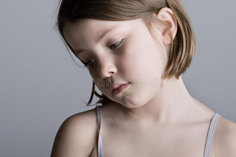 Sad Looking Child against a Grey Background. Shot of a Sad Looking Child against a Grey Background royalty free stock photography