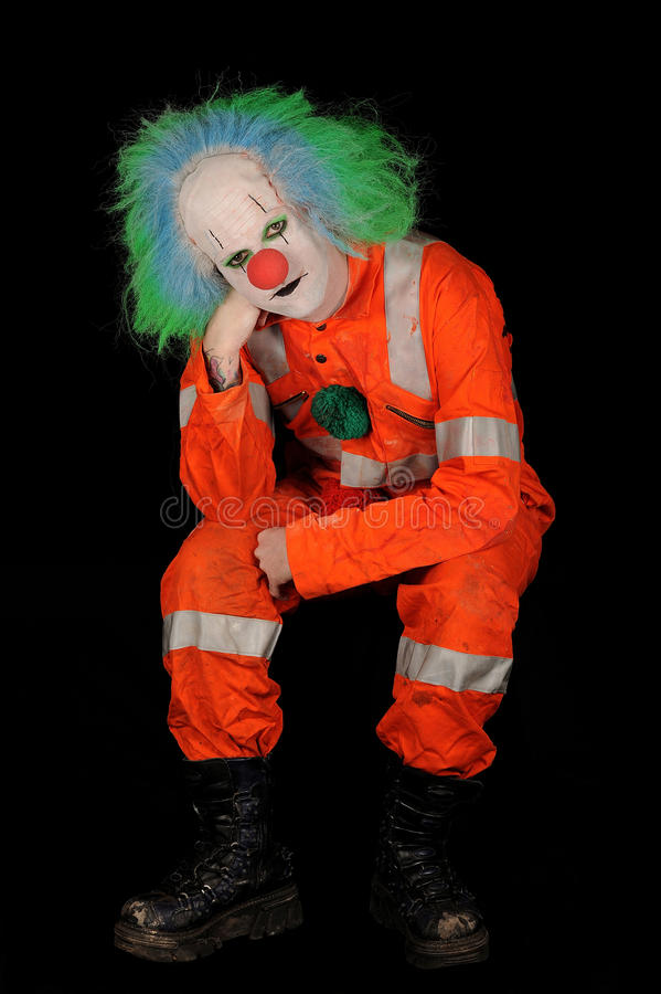 Sad male clown. With painted white face, green wig and costume; black background stock photography