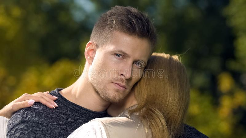 Sad male embracing wife, relationship crisis, psychologist services, therapy stock photography
