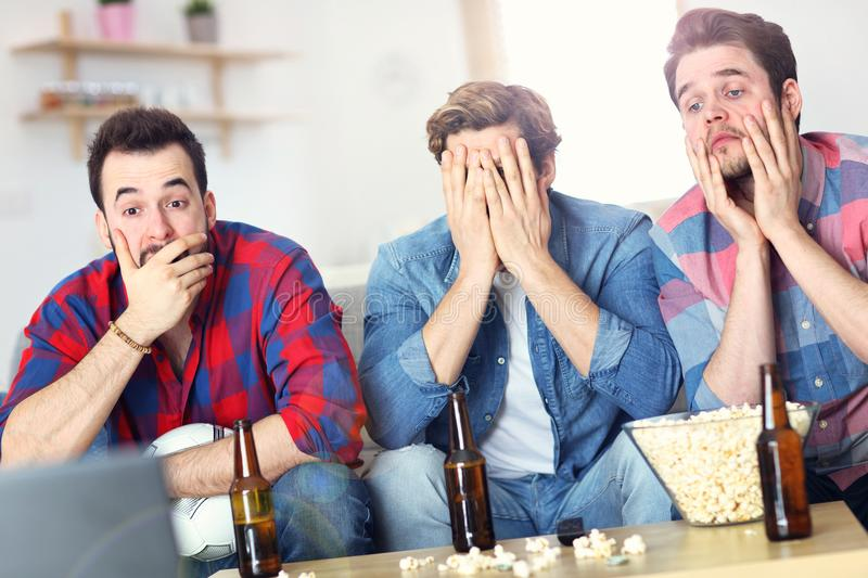Sad male group of friends watching sports on tv at home stock photography