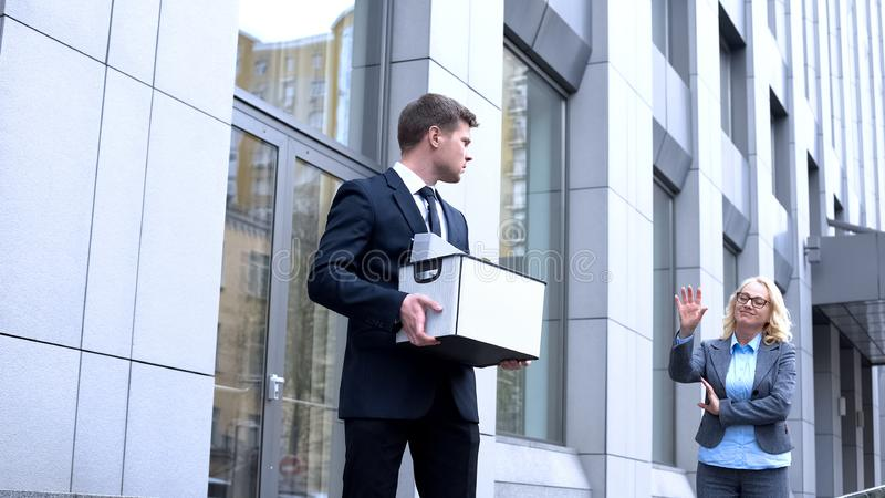 Sad male manager with stuff box looking gloating female boss, company dismissal stock photos
