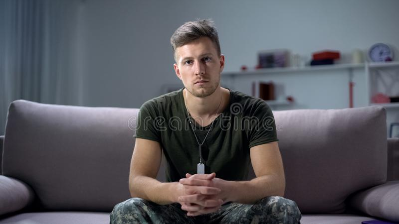 Sad male military sitting on sofa and looking at camera, psychological trauma. Stock photo stock photo