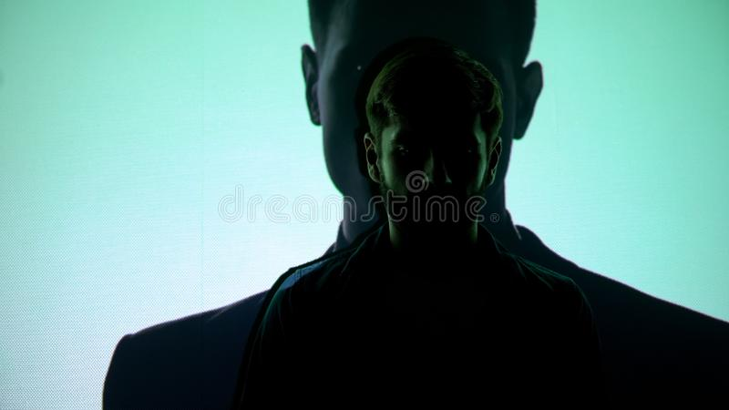 Sad male standing against silhouette of successful businessman, lost dream royalty free stock image