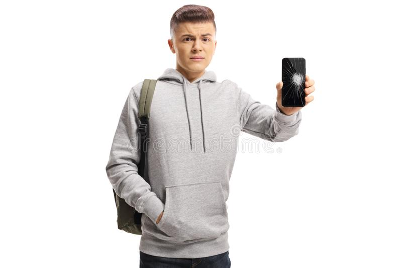 Sad male teenager holding a mobile phone with a broken screen stock image
